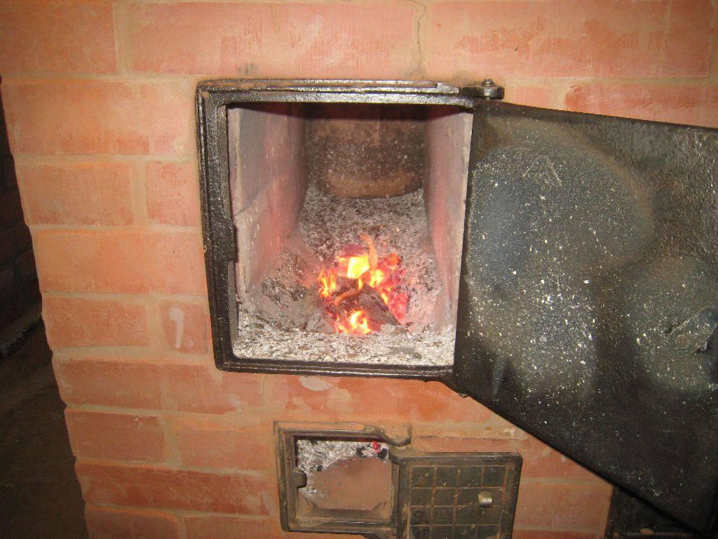 Почему дымит печка при открытии дверцы?